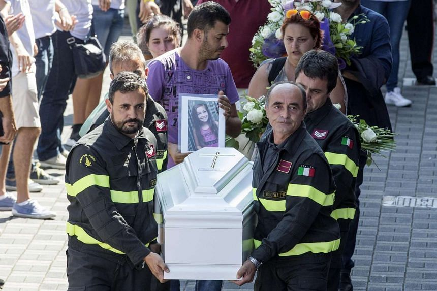 Among the coffins was a small, white casket for nine-year-old Giulia, whose body protected her younger sister, Giorgia, for long enough for the five-year-old to be pulled from the rubble virtually unscathed.