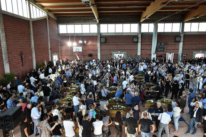 Relatives of earthquake victims gather in a gymnasium arranged in a chapel of rest on Aug 27, 2016.