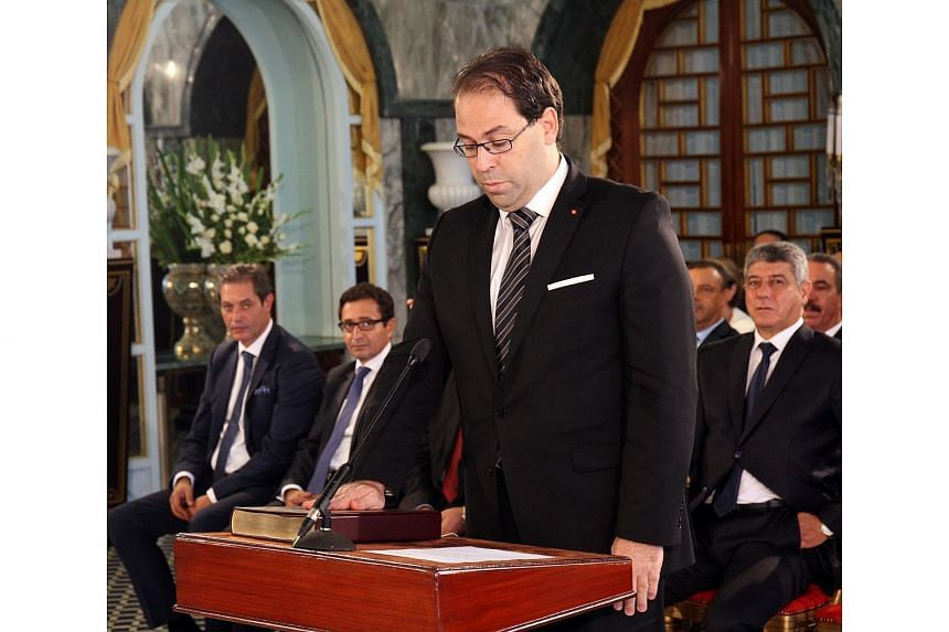 Tunisia's new Prime Minister Youssef Chahed taking an oath of office, during the country's new government swearing-in ceremony at Carthage Palace in the capital Tunis on Aug 27, 2016.