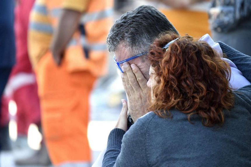 A woman (right) comforts her husband as rescuers recover the body of his mother in Amatrice, Italy, Aug 26, 2016.
