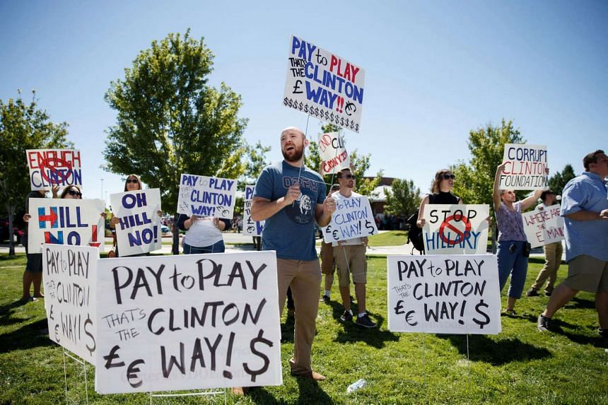 Protesters hold signs before a campaign event with Hillary Clinton, 2016 Democratic presidential nominee (not pictured) at Truckee Meadows Community College in Reno, Nevada, US, on Aug 25, 2016.