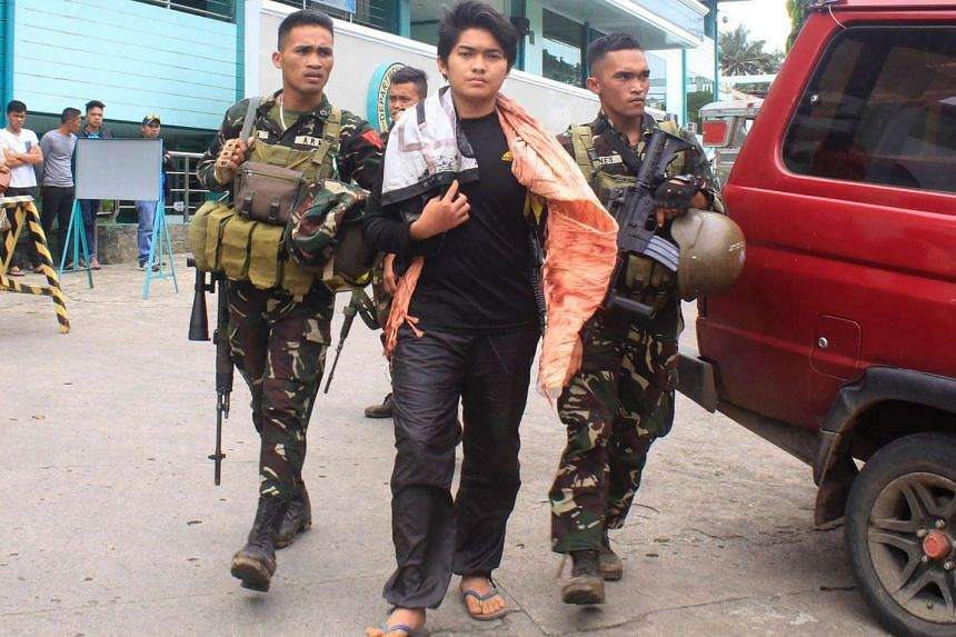 Philippine soldiers escorting Maute extremist group member Hassim Balawag Maute alias Apple Jehad to a military vehicle in Marawi City in the southern island of Mindanao, a day after he and others were arrested at a military checkpoint and were later