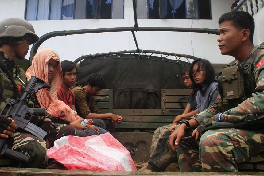 Philippine soldiers guarding members of the Maute extremist group aboard a military vehicle in Marawi City in the southern island of Mindanao, a day after they were arrested at a military checkpoint and who were later on freed by their comrades in a