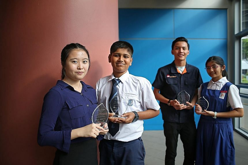 From left: Students Ng Hui, 17; Abdur Rahman Galib, 13; Muhammad Izzul Isam Jamil, 17, and Faustina Anne Francisco, 13, received awards from the four self-help groups for doing well at different levels of national examinations last year.