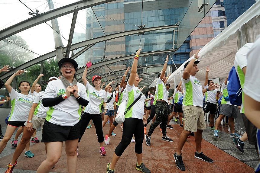 Race participants taking part in a mass workout at the CapitaLand Commercial Trust Eco Race yesterday. The EDB team came in first in the race, with Fitness First and JP Morgan tied in second.