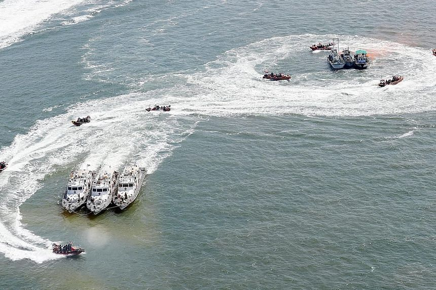 High-speed boats from the Korea Coast Guard and navy surround vessels simulating foreign boats fishing illegally in South Korean waters during an exercise in the West Sea last Friday. A vast number of Chinese boats allegedly cross into South Korean w