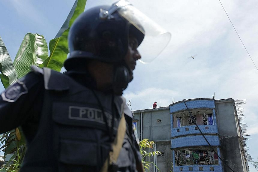 Bangladeshi police standing guard outside a militant hideout in Narayanganj, 25km south of Dhaka yesterday, where the police gun battle against the extremists took place.