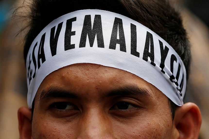 """A student activist sports his message on a headband before the march calling for the arrest of """"Malaysian Official 1"""" in Kuala Lumpur yesterday."""