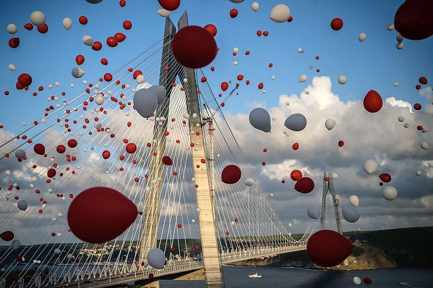 Balloons flying past the Yavuz Sultan Selim Bridge at its opening on Friday. The 1.4km bridge creates a new link across the Bosphorus Strait, which divides Asia and Europe. President Erdogan hopes to use such large-scale projects to drive Turkey's ec