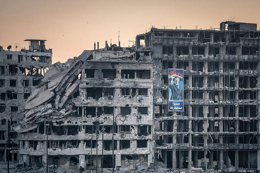 A poster of President Bashar al-Assad on a destroyed shopping mall in Homs. Despite many offensives, peace conferences and foreign interventions, Syria's civil war shows no sign of ending, say experts.