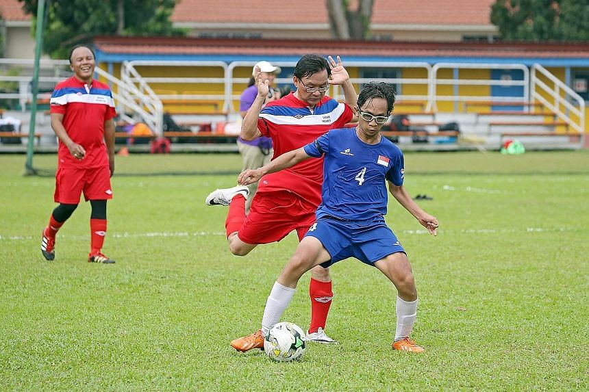 The friendly match between the Cerebral Palsy Football team and the Parliament team went ahead yesterday despite hazy conditions. Mr Shafiq Ariff (in blue), 23, is seen shielding the ball from MP Chong Kee Hiong (Bishan-Toa Payoh GRC) as MP Muhamad F