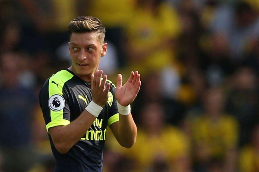 Arsenal's Mesut Ozil celebrates scoring their third goal.
