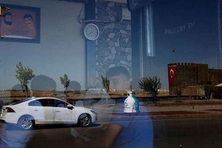 Historical city walls are reflected on the window of a tea house in Sur district of Diyarbakir on July 11.