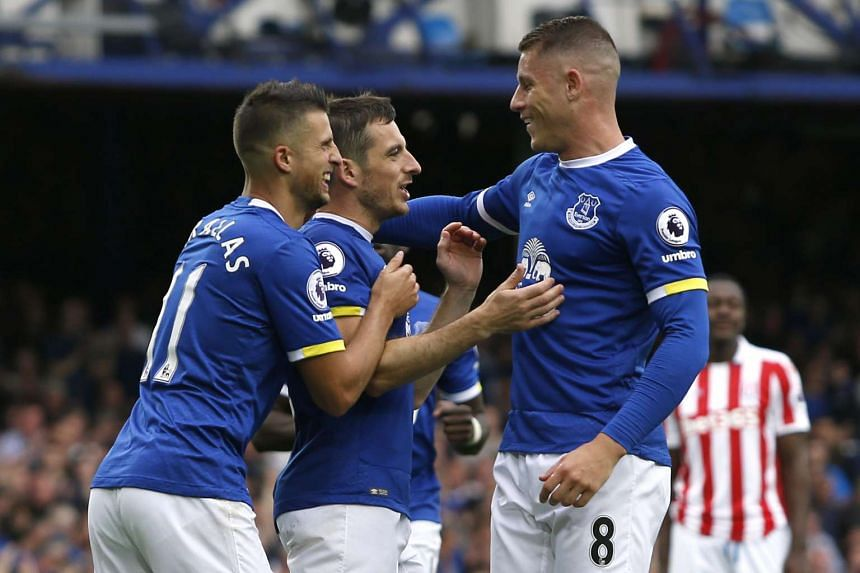 Everton's Leighton Baines celebrates their first goal with Ross Barkley and Kevin Mirallas, which was an own goal scored by Stoke City's Shay Given.