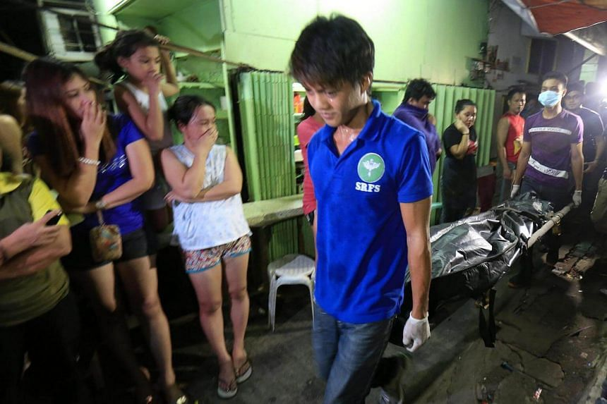 Filipino residents view a dead body of an alleged drug dealer killed during a police operation against illegal drugs in Manila, Philippines on Aug 23.