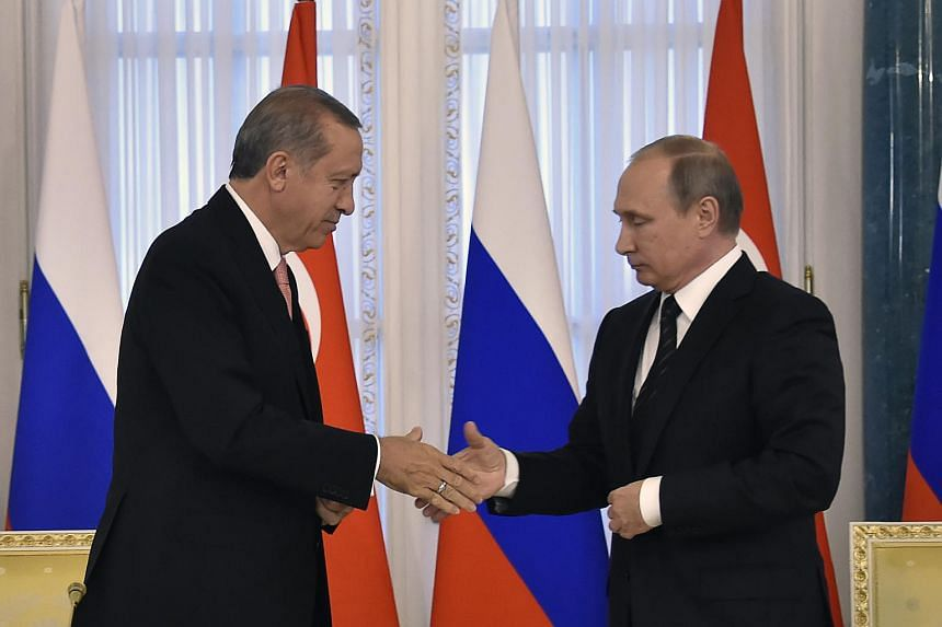 Russian President Vladimir Putin (right) shakes hands with his Turkish counterpart Recep Tayyip Erdogan during their press conference in Konstantinovsky Palace on Aug 9, 2016.