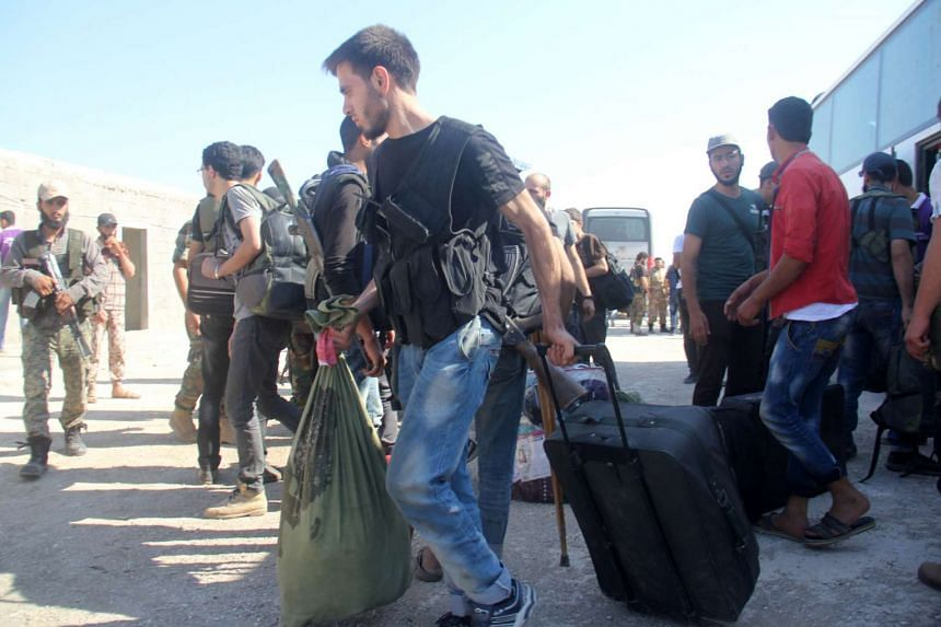 Syrian rebel fighters and their families collect their bags from a coach on Aug 27, 2016, upon their arrival in the rebel-held northwestern city of Idlib.