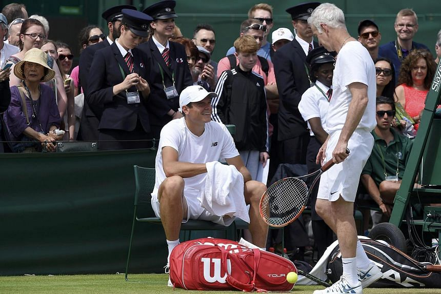 John McEnroe (right) speaking with Milos Raonic during a practice session at Wimbledon, on July 9, 2016.