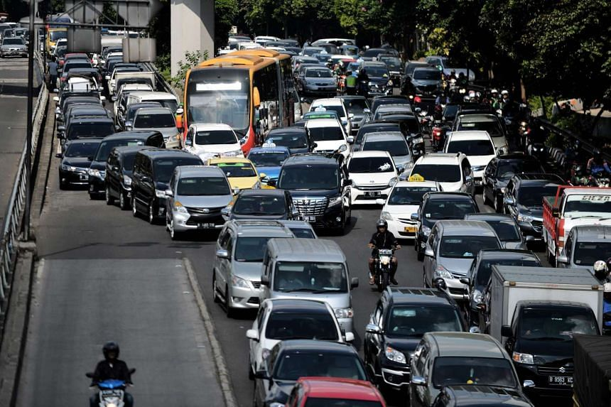 Vehicles commute on a road during afternoon rush hour in Jakarta.