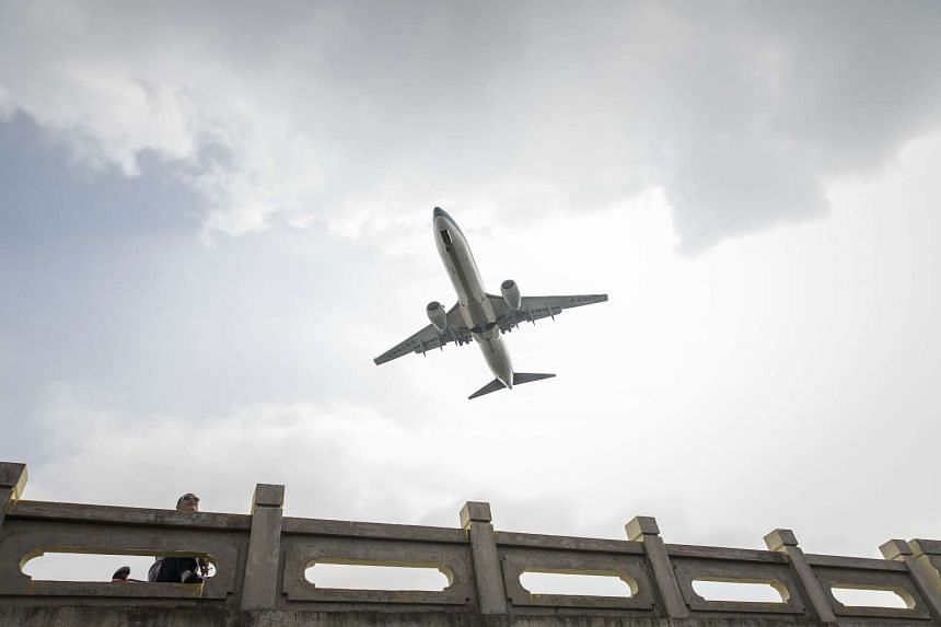 A China Southern Airlines aircraft flying over a pedestrian bridge as it approaches to land at Hongqiao Airport in Shanghai, China, on Oct 23, 2015.
