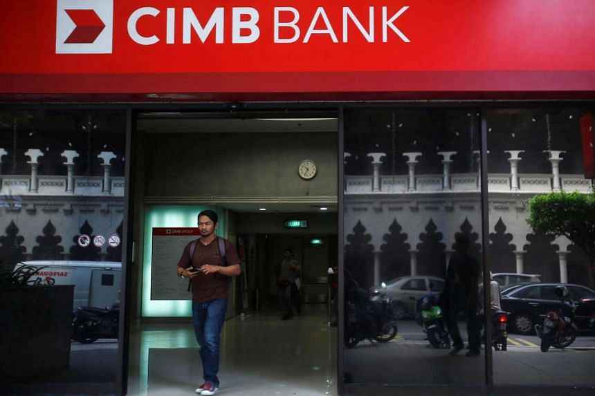 A man walks out of a CIMB Bank in Kuala Lumpur. CIMB posted a 36 per cent jump in second-quarter profit.