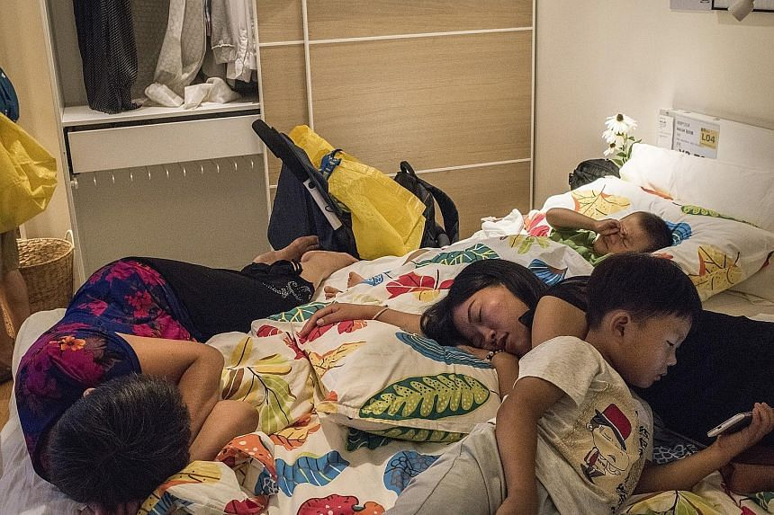 A family resting on a display bed at an Ikea store in Beijing.