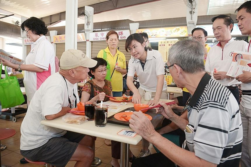 MacPherson MP Tin Pei Ling (centre) and grassroots leaders speaking to patrons at the food centre at 117, Aljunied Avenue 2 yesterday. They gave out leaflets and insect repellent, and urged people to keep their premises mosquito-free. Ms Tin said she