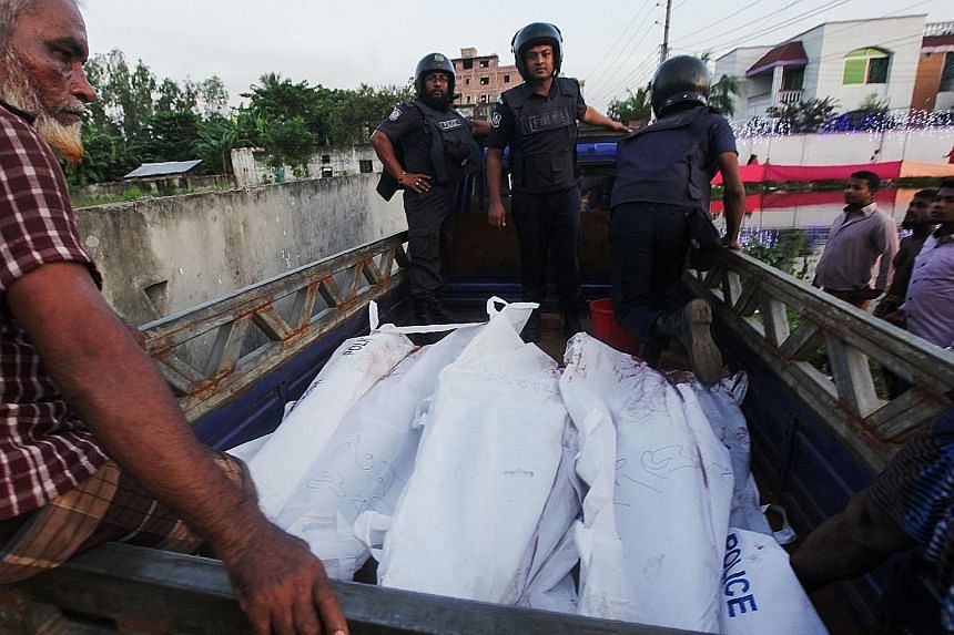 Bangladesh policemen escorting the bodies of suspected militants following an operation to storm a militant hideout in Narayanganj, some 25km south of Dhaka yesterday. Bangladeshi Prime Minister Sheikh Hasina said the successful raid will improve Ban