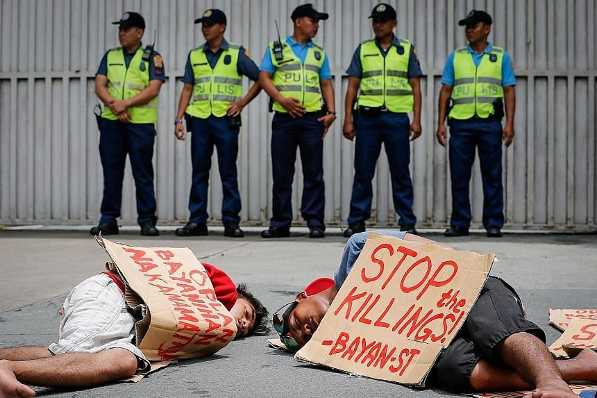 Protesters mimicking an extrajudicial killing as police officers stand guard in front of the Philippine National Police headquarters in Camp Crame, Quezon City,near Manila. President Duterte won a landslide election victory in May, with a promise to