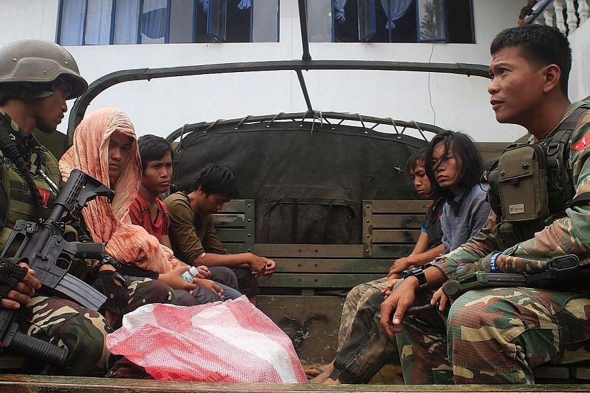 Philippine soldiers guarding members of the Maute extremist group on a military vehicle in Marawi city on the southern island of Mindanao last Tuesday, a day after they were arrested at a military checkpoint when bombs and pistols were found in the v