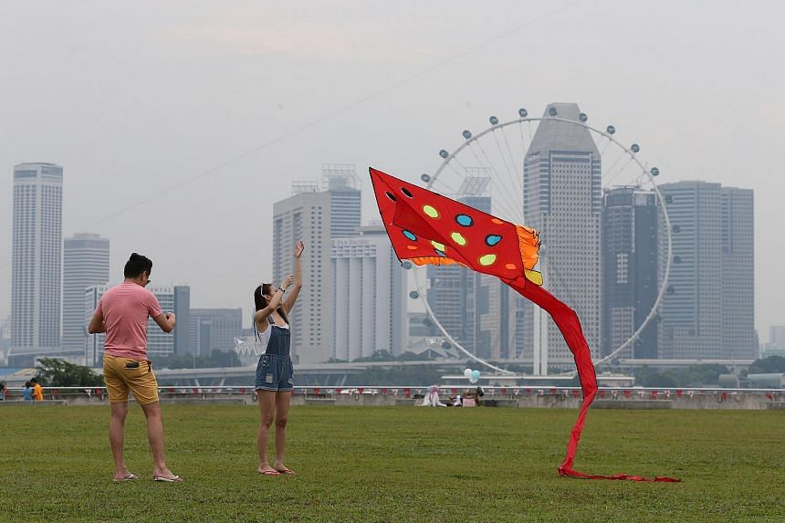 People enjoying outdoor activities at Marina Barrage on Aug 27, 2016, despite hazy conditions.