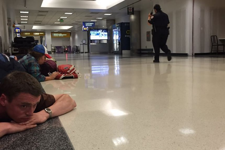 Passengers take cover after unconfirmed reports of shots being fired at Los Angeles International airport.