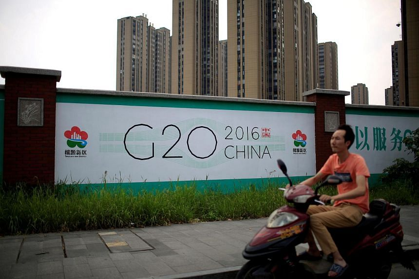 A man rides an electronic bike past a billboard for the upcoming G-20 summit in Hangzhou, Zhejiang province, on July 29, 2016.