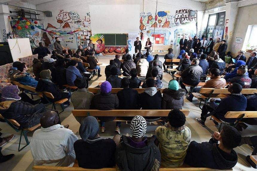 "This photo taken on Feb 24 shows migrants following lessons for refugees and asylum seekers on German legislation in a hall of the ""Bayernkaserne"" reception center in Munich, southern Germany.  Germany expects up to 300,000 asylum seekers to arrive t"