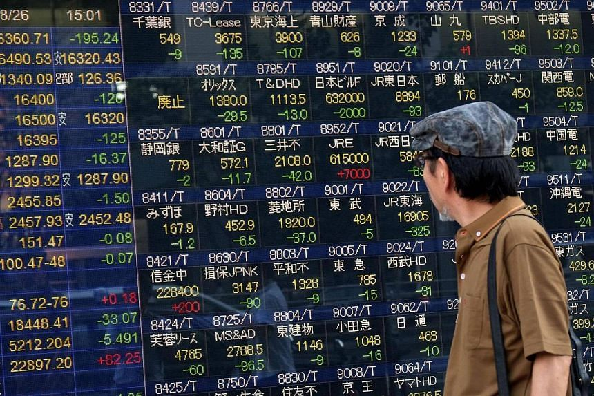 A man looking at an electric quotation board displaying the Nikkei key index of the Tokyo Stock Exchange in Tokyo on Aug 26, 2016.