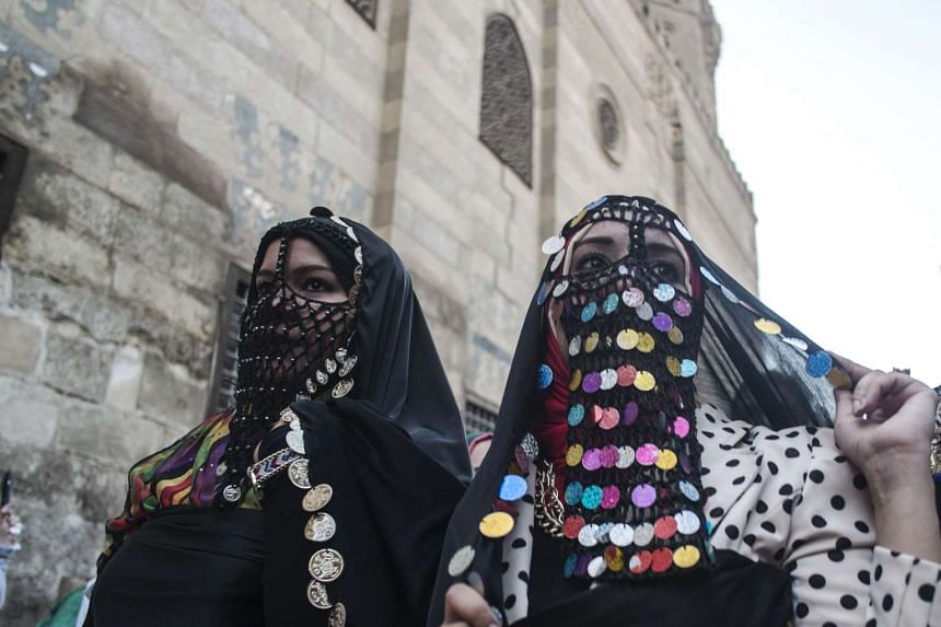 Egyptian women dressed in their country's traditional clothing walk at al-Mezz street during a celebration in old Cairo on June 2, 2016.