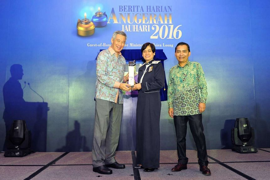 PM Lee Hsien Loong giving the Berita Harian Achiever of the Year Award to Madam Zuraidah Abdullah, along with BH editor Saat Abdul Rahman, at the Furama RiverFront Hotel on Aug 30, 2016.