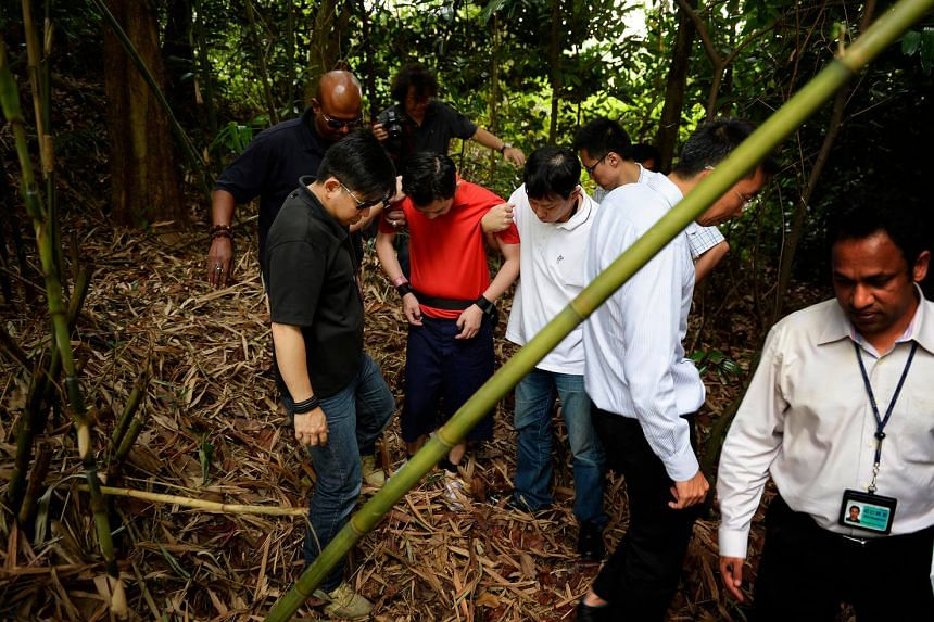 Lee Sze Yong (in red), who allegedly masterminded the Sheng Siong kidnapping case, seen here with police investigators at Sembawang Park in 2014.