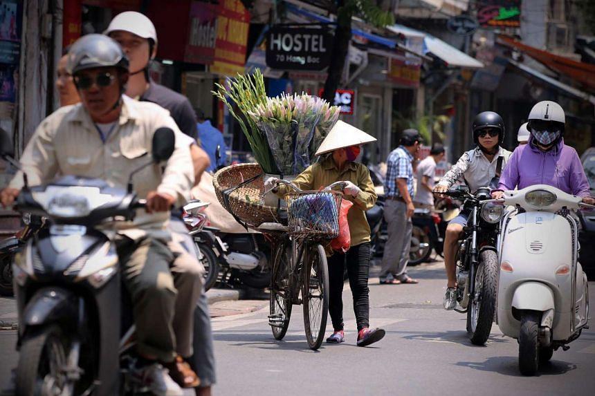 A street vender walks at a street in Hanoi, Vietnam, August 26.