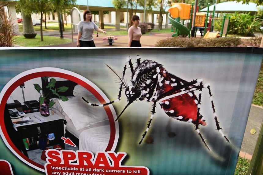 Residents walk past a public service announcement banner against the spread of Aedes mosquitoes, a carrier for the Zika virus, at Aljunied Crescent neighbourhood in Singapore on August 29.