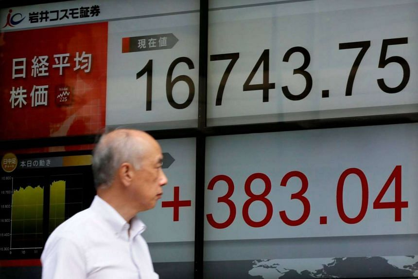 A man walks past a display showing Tokyo's Nikkei Stock Average on Aug 29. Asian shares bounced on Tuesday (Aug 30) as doubts the Federal Reserve really would hike rates as soon as September undermined the US dollar.