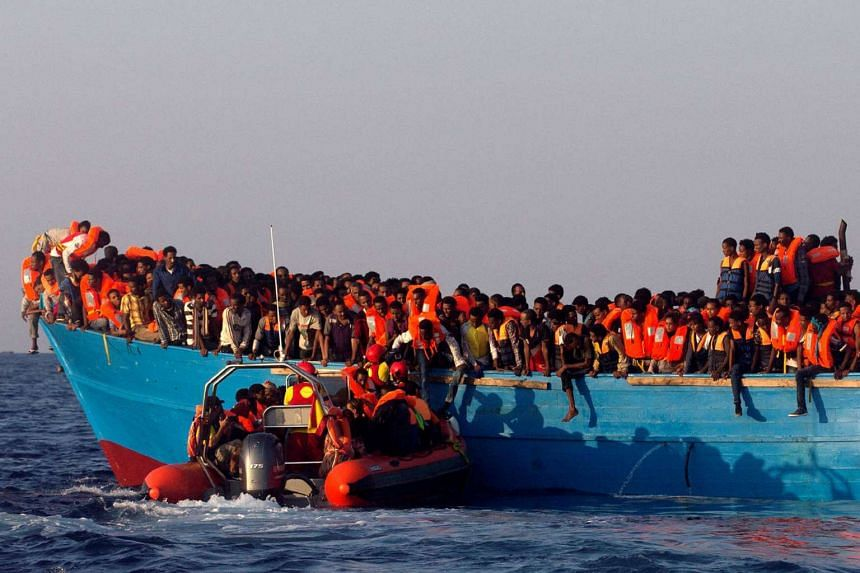 A rescue boat of the Spanish NGO Proactiva approaches an overcrowded wooden vessel with migrants from Eritrea, off the Libyan coast in Mediterranean Sea.