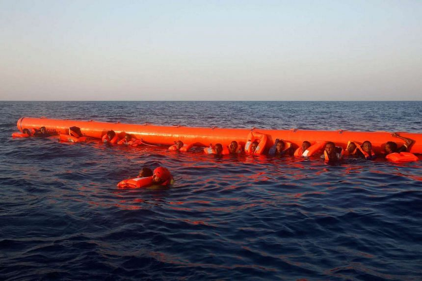 A member of the Spanish NGO Proactiva rescues a migrant from Eritrea as others cling to a floatation rescue device, off the Libyan coast in Mediterranean Sea.