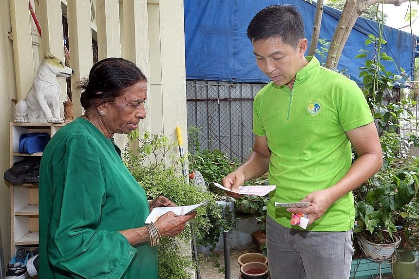 Mr Tan speaking with a resident while visiting homes in Joo Chiat Place and Lorong 101 Changi yesterday.