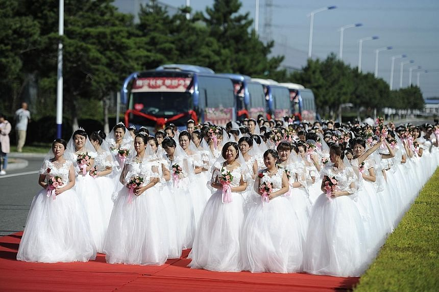 Anxious brides, all 162 of them, waiting for their wedding ceremony to begin at the manufacturing base of the CRRC Changchun Railway Vehicles Company in Changchun, capital of Jilin province, in north-east China. The railway carriage maker held a mass