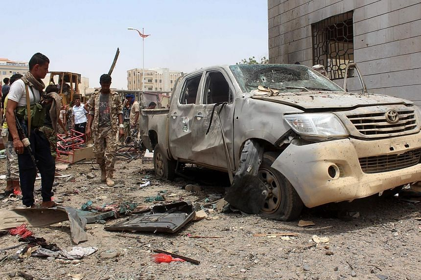 A wrecked vehicle and debris at the site of the car bombing at an army recruitment centre in Aden yesterday. ISIS has claimed the attack on its official propaganda outlet.