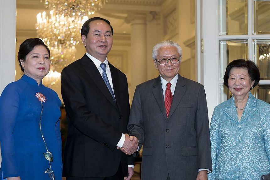 Vietnam's President Quang and his wife, Madam Nguyen Thi Hien with President Tan and Mrs Mary Tan at the Istana yesterday. PM Lee Hsien Loong and Vietnamese President Tran Dai Quang meeting at the Istana yesterday. President Tony Tan Keng Yam raising
