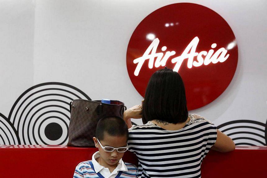 Customers wait at an Air Asia ticket counter at Kuala Lumpur International Airport in Sepang, Malaysia.