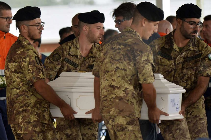 Soldiers carry the coffin of a baby in a tent complex in Amatrice, central Italy, on Aug 30, 2016, prior to a funeral ceremony for the victims.