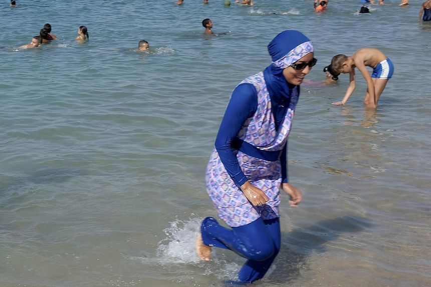 A woman wearing a burkini wades in the sea on a beach in Marseille, France, on Aug 27, 2016.